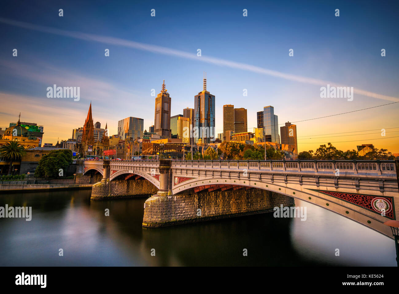 Sunset over skyline of Melbourne downtown, Princess Bridge and Yarra River - Stock Image