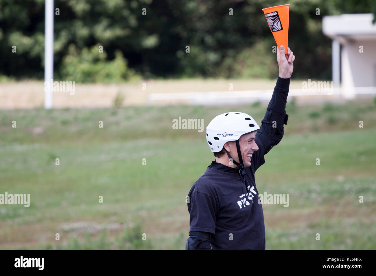 Competitor in a downhill skateboard slalom holding up a cone to indicate it had been touched - Stock Image