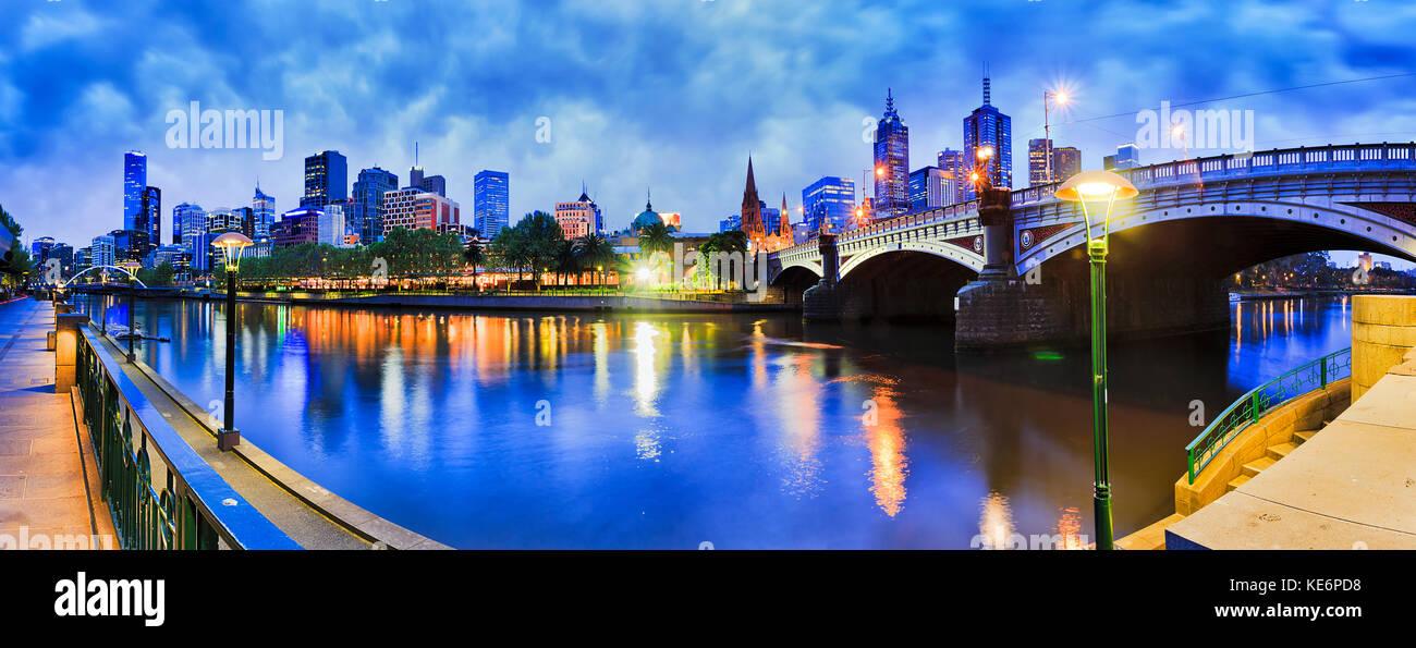 Princes bridge across Yarra river to Flinders station and Melbourne CBD dark at sunrise with bright street lights - Stock Image