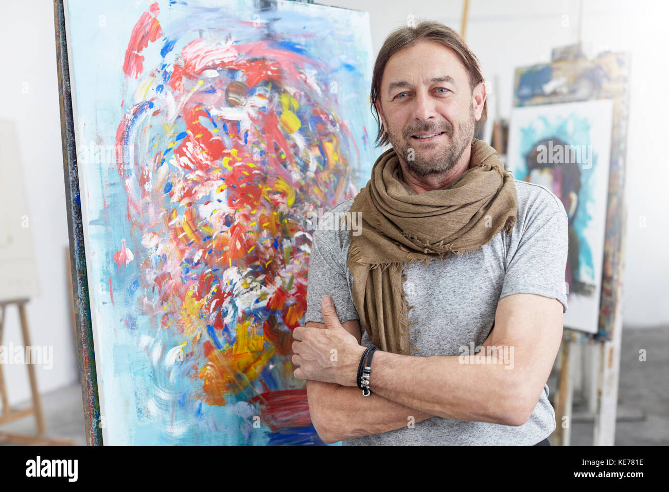 Portrait smiling, confident artist standing at abstract painting in art class studio - Stock Image