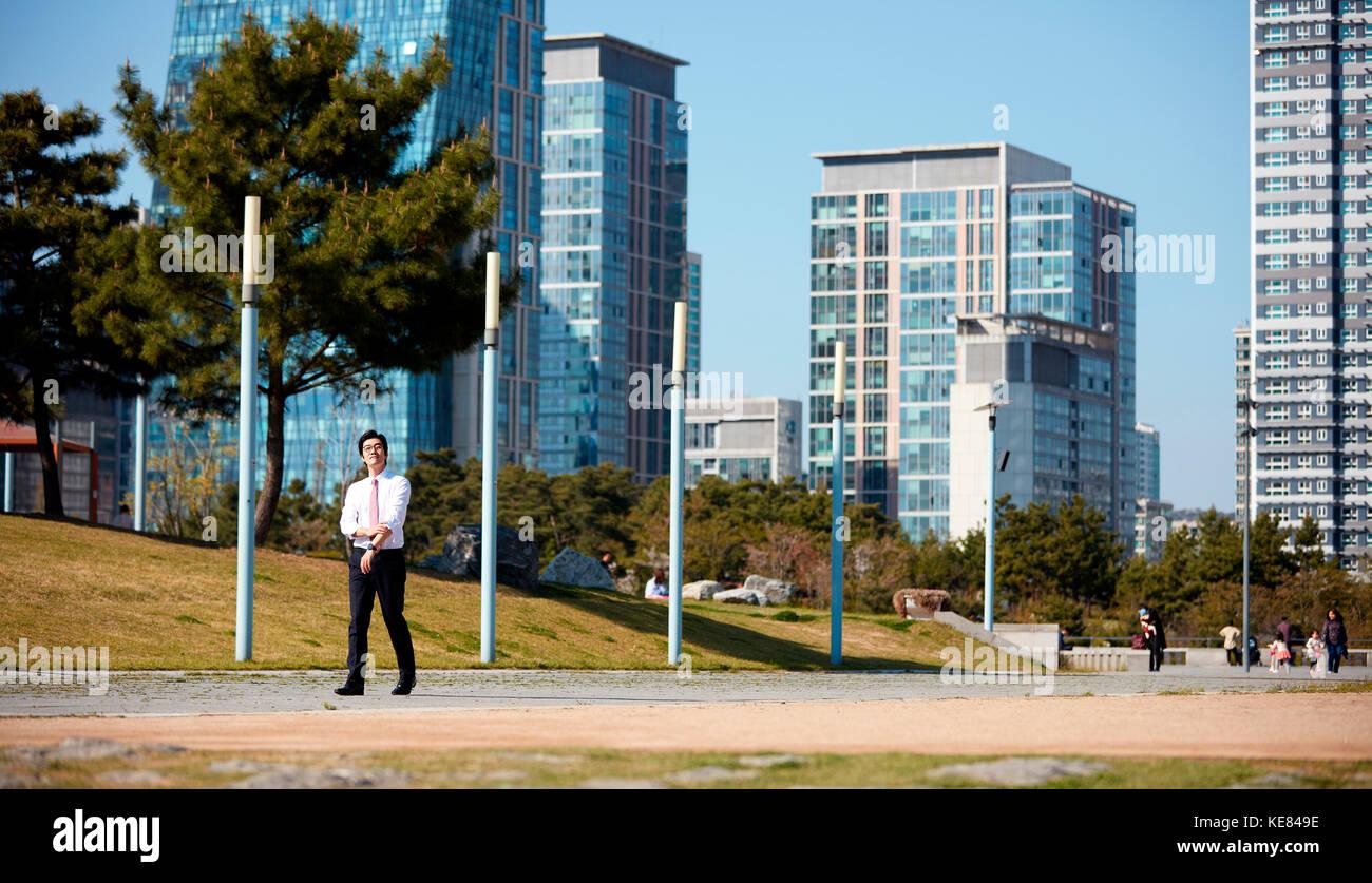Businessman talking a walk at park - Stock Image