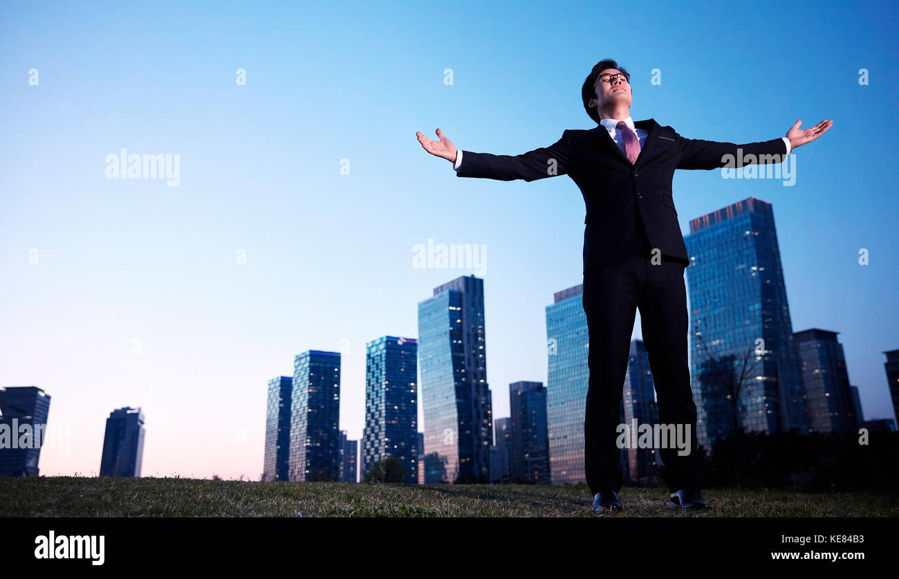 Businessman standing opening his arms in city at night - Stock Image