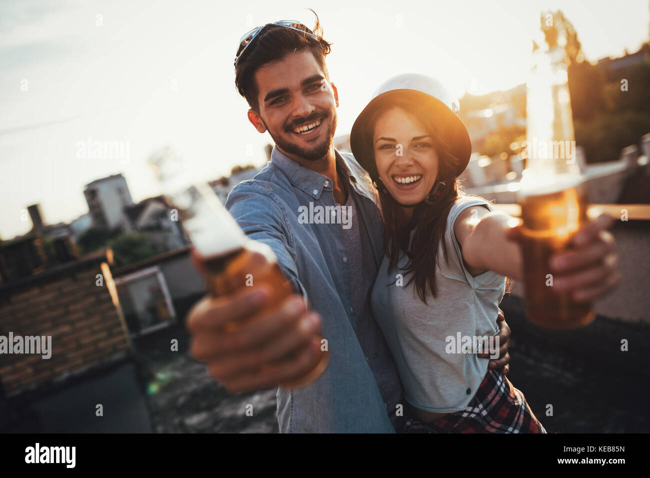 Young happy couple toasting with beer outdoors - Stock Image