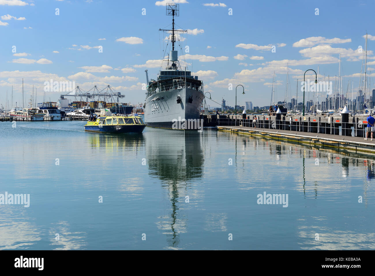 Passenger ferry arriving at Gem Pier (with HMAS Castlemaine in background) in Williamstown, a suburb of Melbourne, - Stock Image