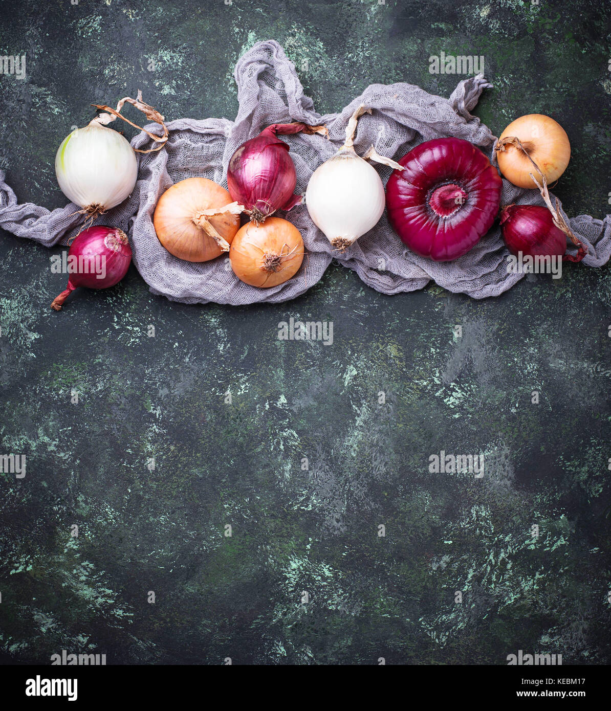 Various type of onions on green background.  - Stock Image