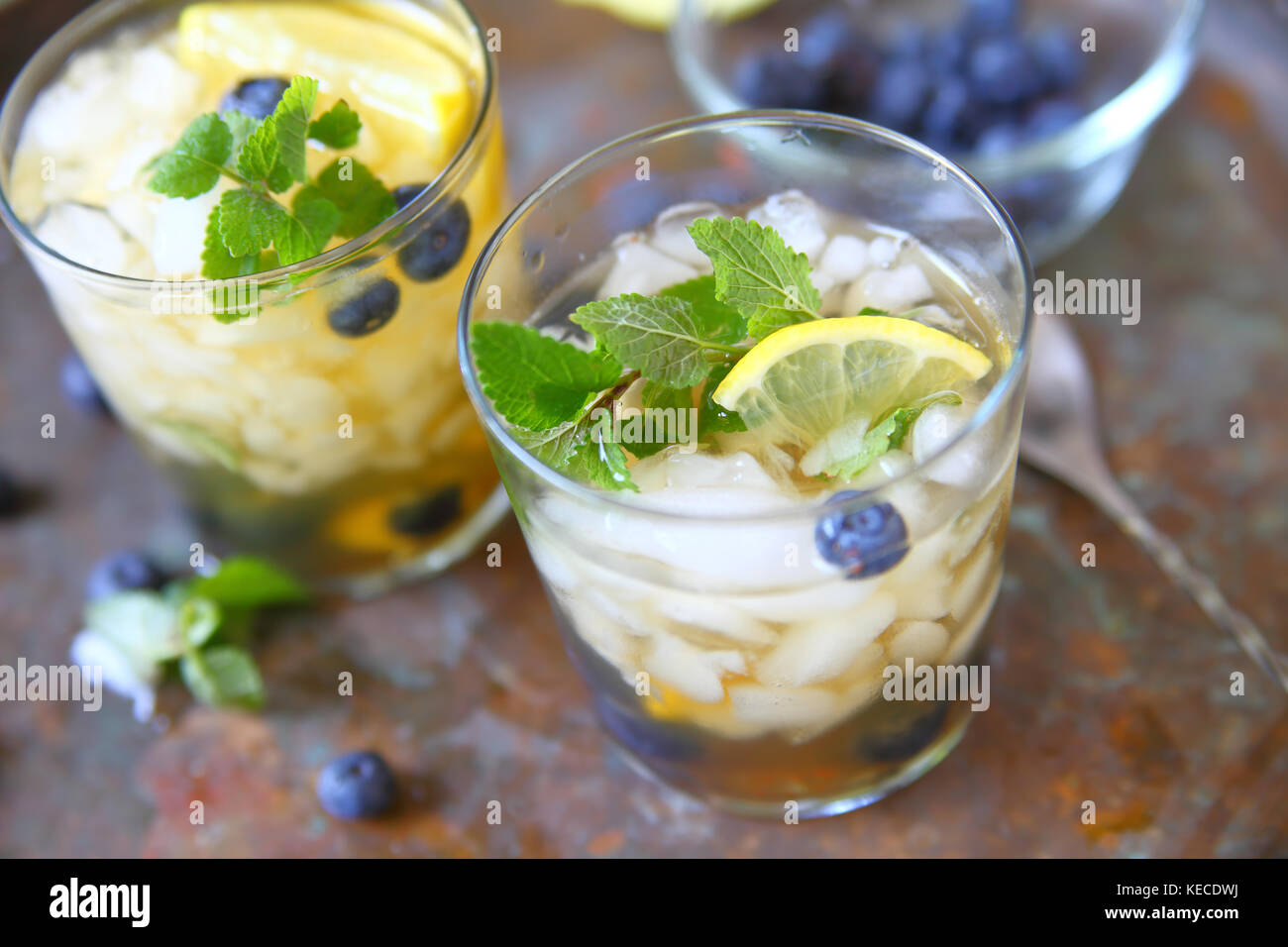 Glasses of green tea with crushed ice, lemon, blueberries and mint - Stock Image