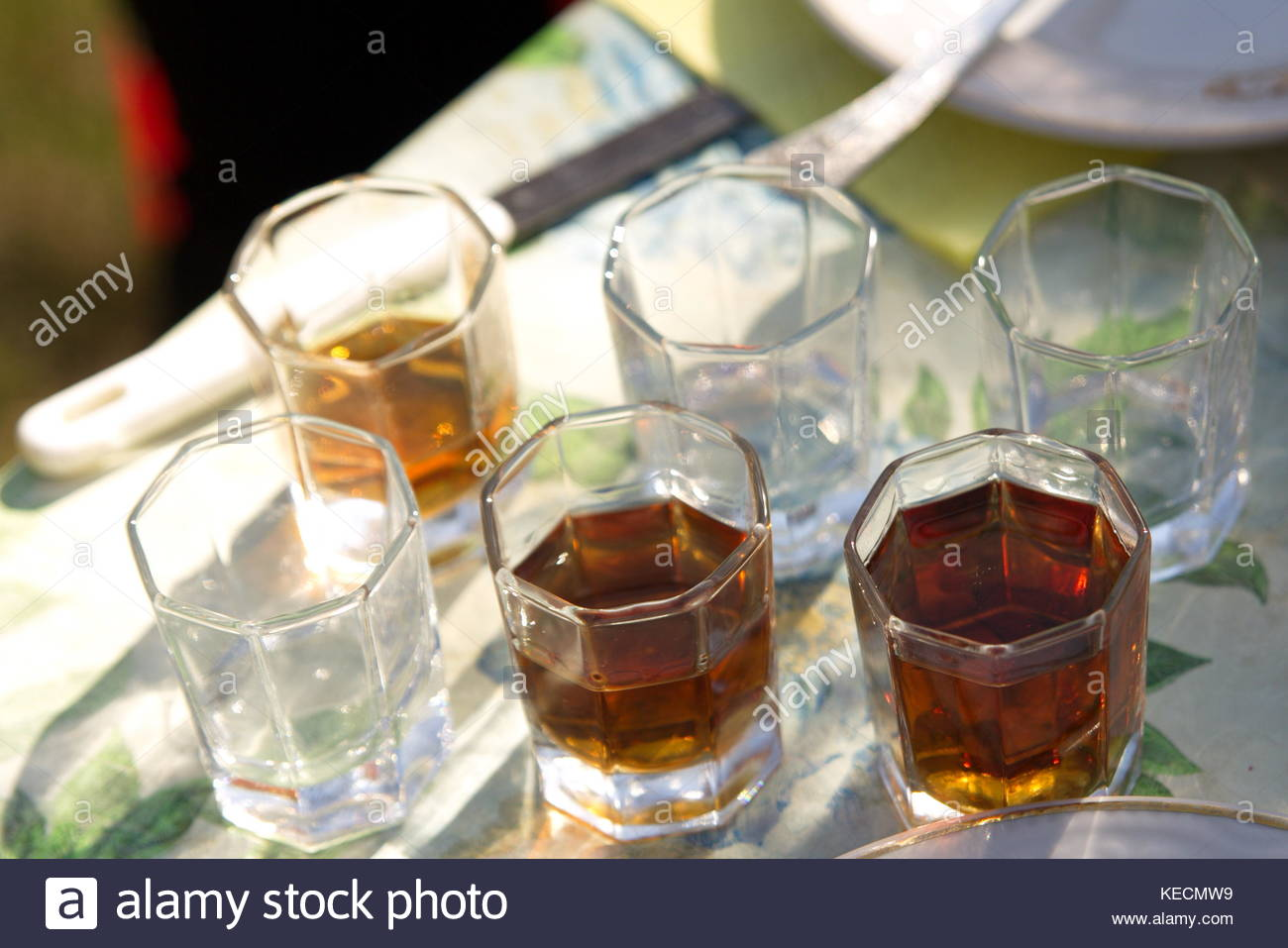 Empty and full glasses of wine on the table outside on the barbeque - Stock Image