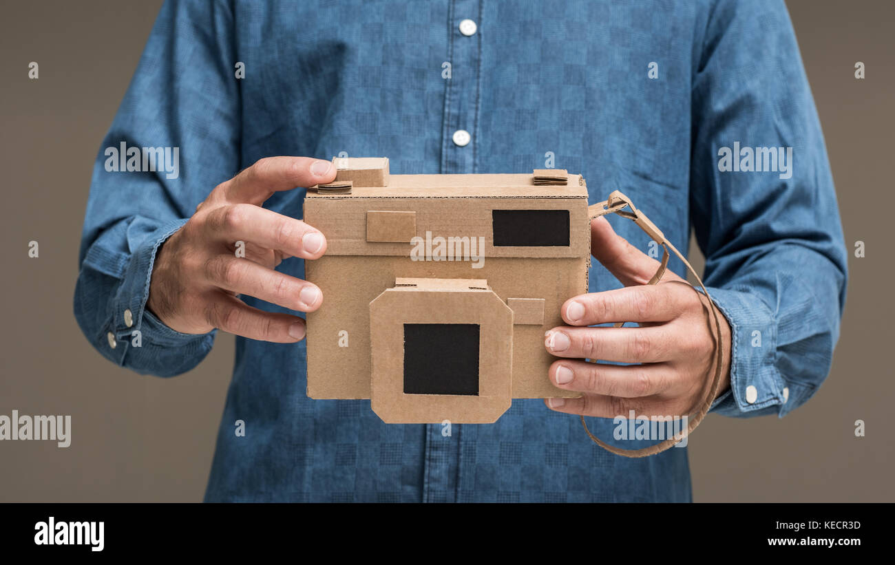 Photographer holding an handmade eco-friendly cardboard camera, crafts and creativity concept Stock Photo