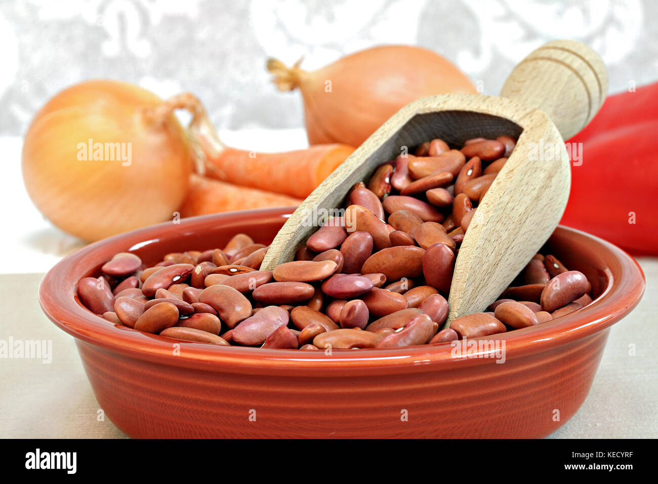Raw kidney beans with a wooden scoop in a bowl, selective focus macro with copy space. - Stock Image