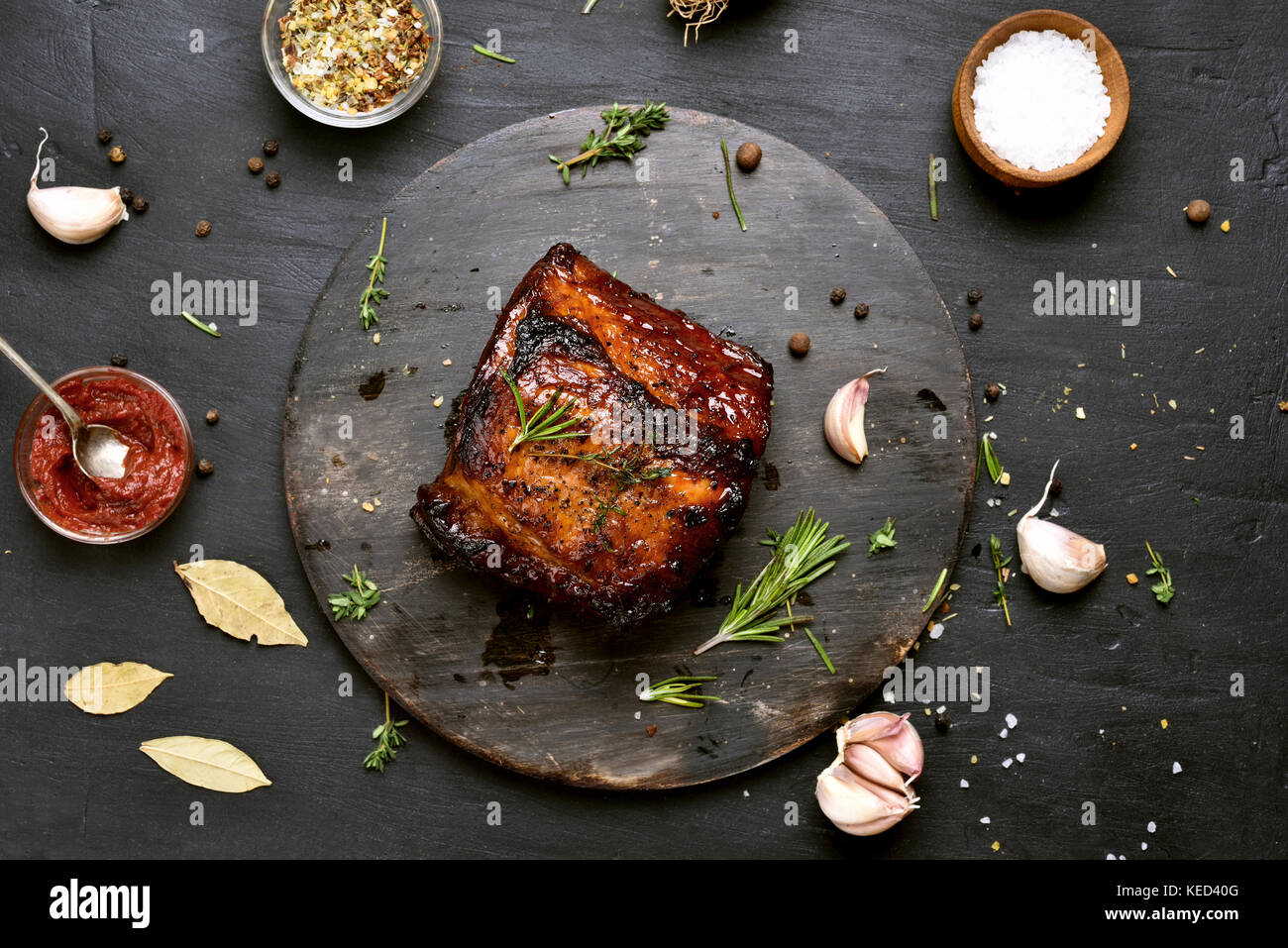 Barbecue pork, grilled meat on dark background. Top view - Stock Image