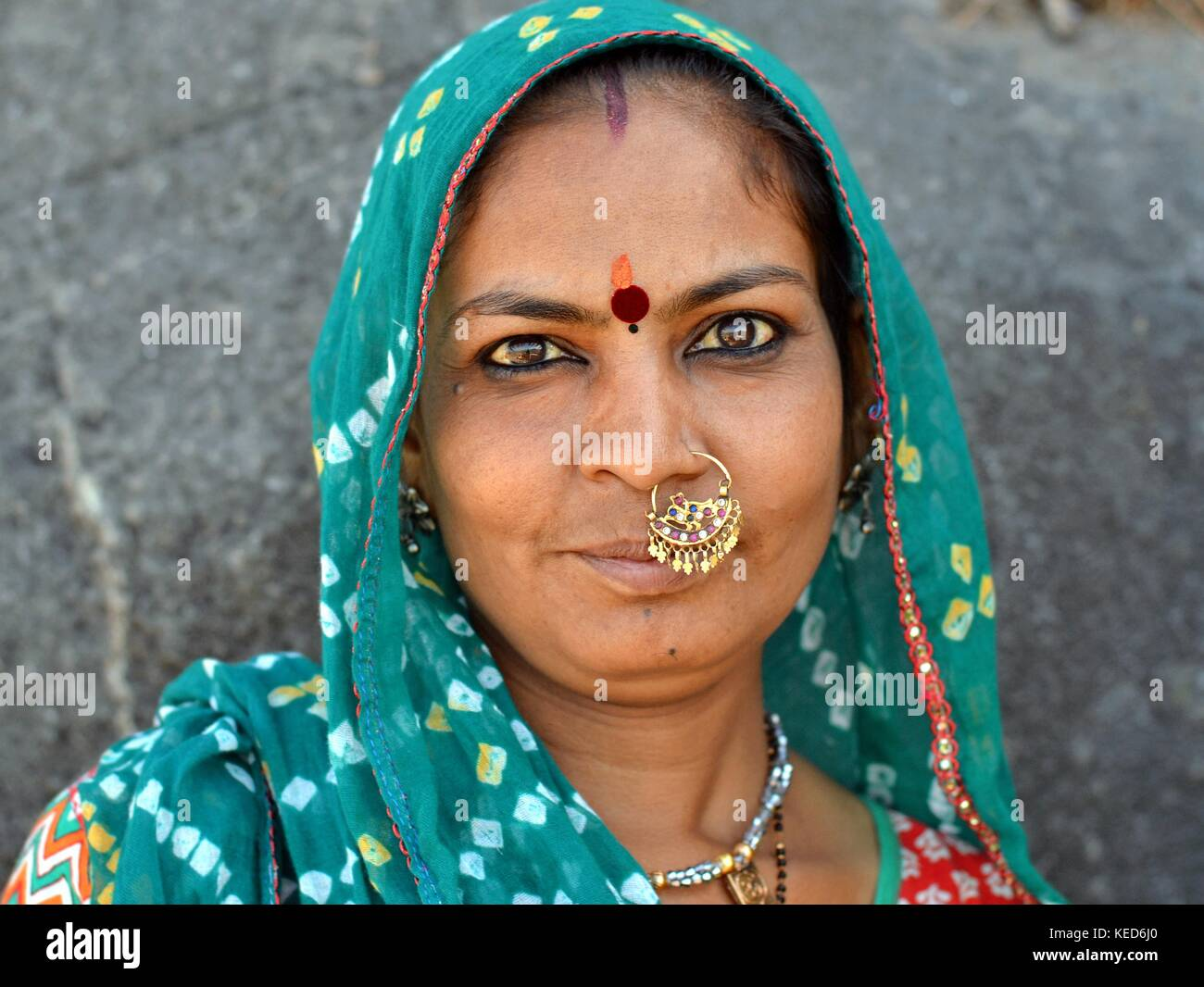 Head shot of a middle-aged Gujarati woman with green dupatta and precious traditional Indian nose jewellery - Stock Image