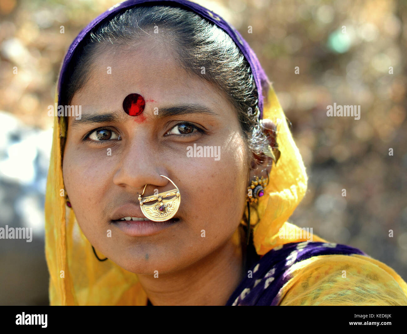 Head shot of a young Gujarati woman with yellow dupatta and precious traditional Indian nose jewellery - Stock Image