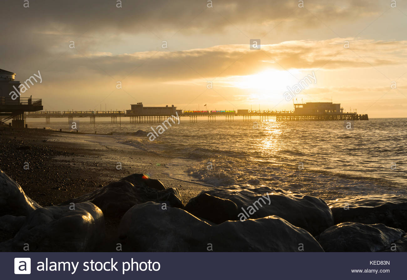 Sun rising over the pier and sea in Autumn in Worthing, West Sussex, England, UK. - Stock Image