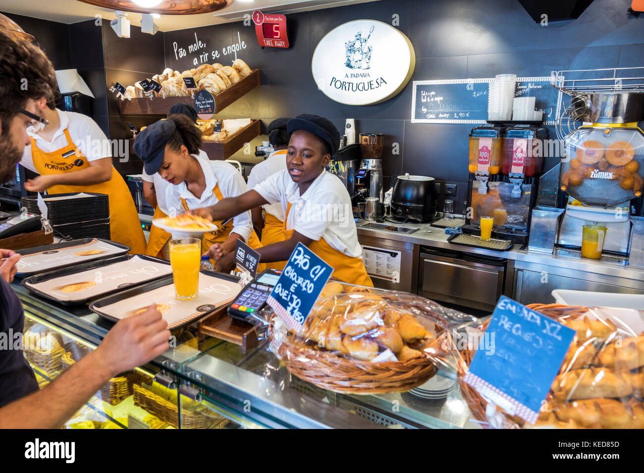 Lisbon Portugal Marquis of Pombal Square Padaria Portuguesa bakery cafe counter server customer bread Black woman - Stock Image
