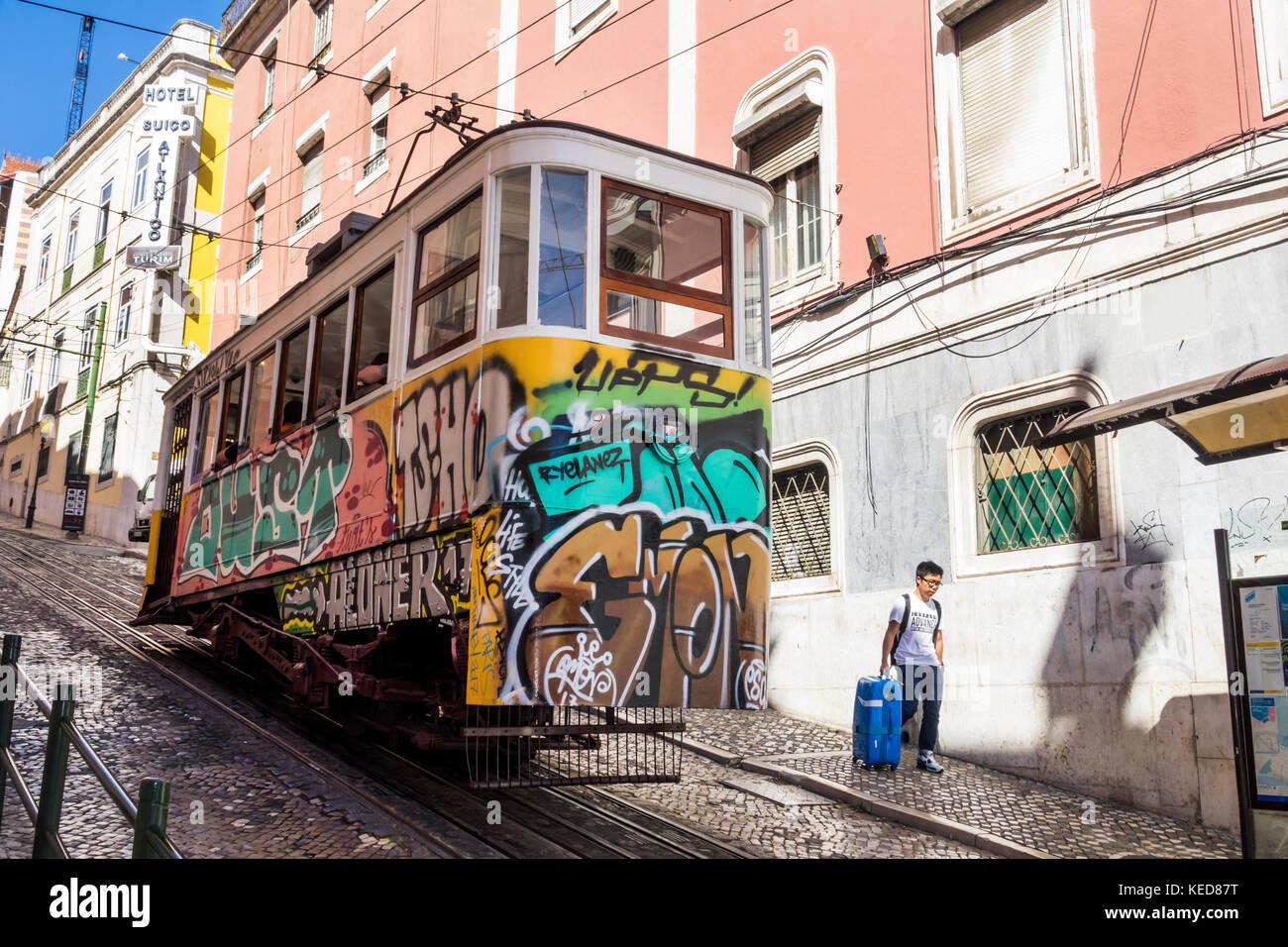 Lisbon Portugal Restauradores Square Ascensor da Gloria Elevador tram funicular railway Asian man luggage suitcase - Stock Image