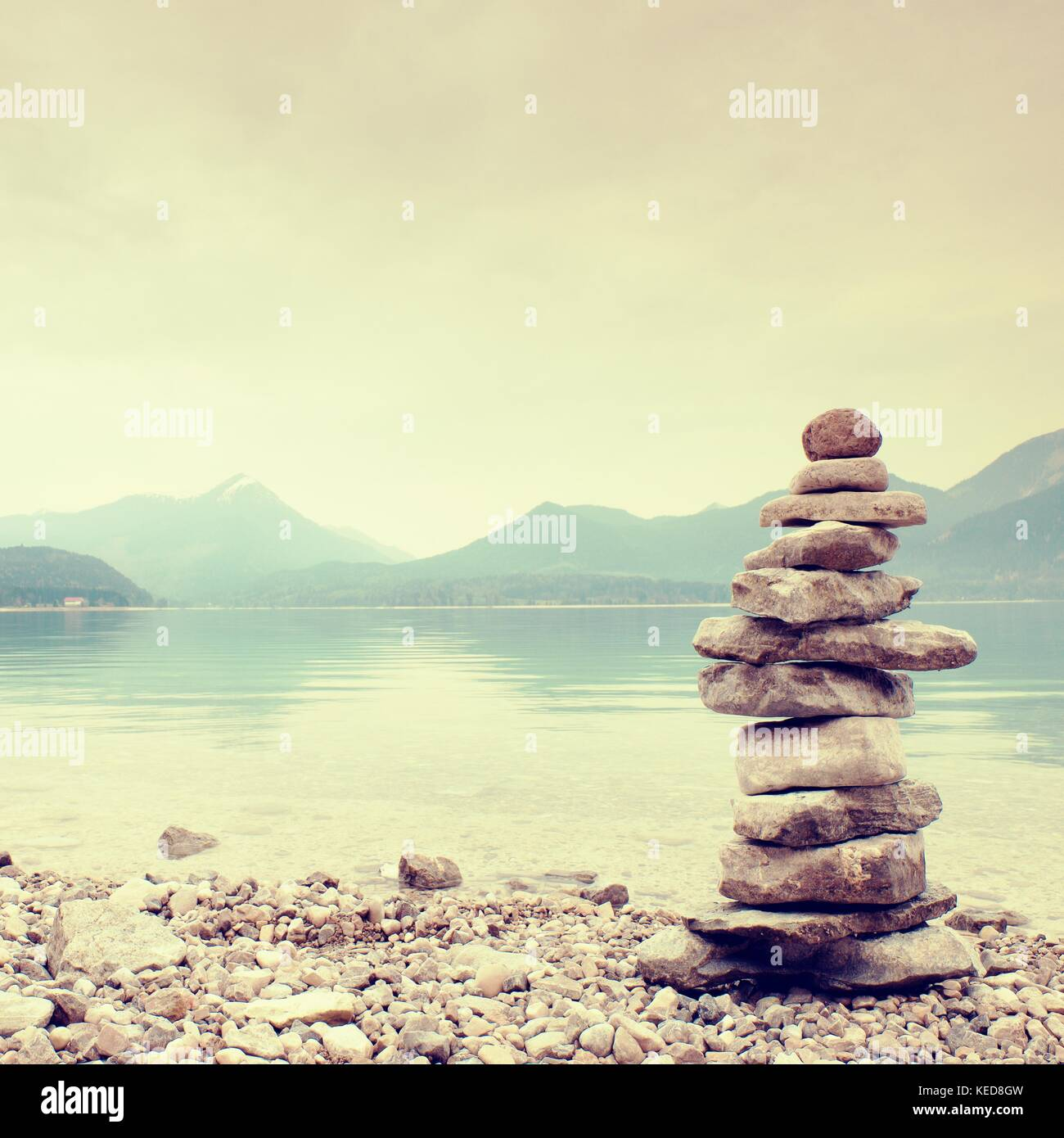 Balanced stone pyramide for memory. Stony shore of blue water of mountain lake with level mirror. Children built - Stock Image