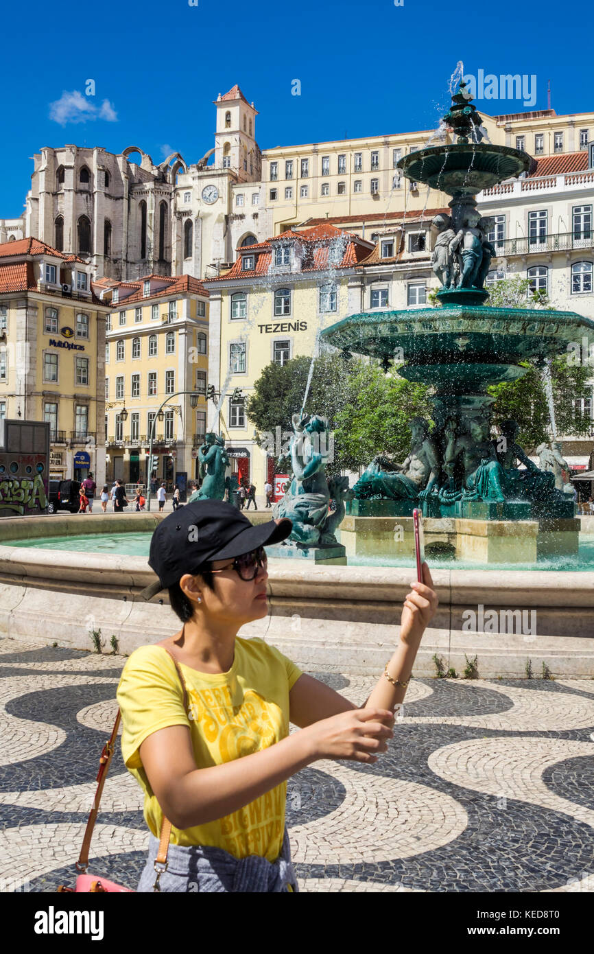 Lisbon Portugal Rossio Square Pedro IV Square fountain skyline view pavement Asian woman selfie smartphone - Stock Image