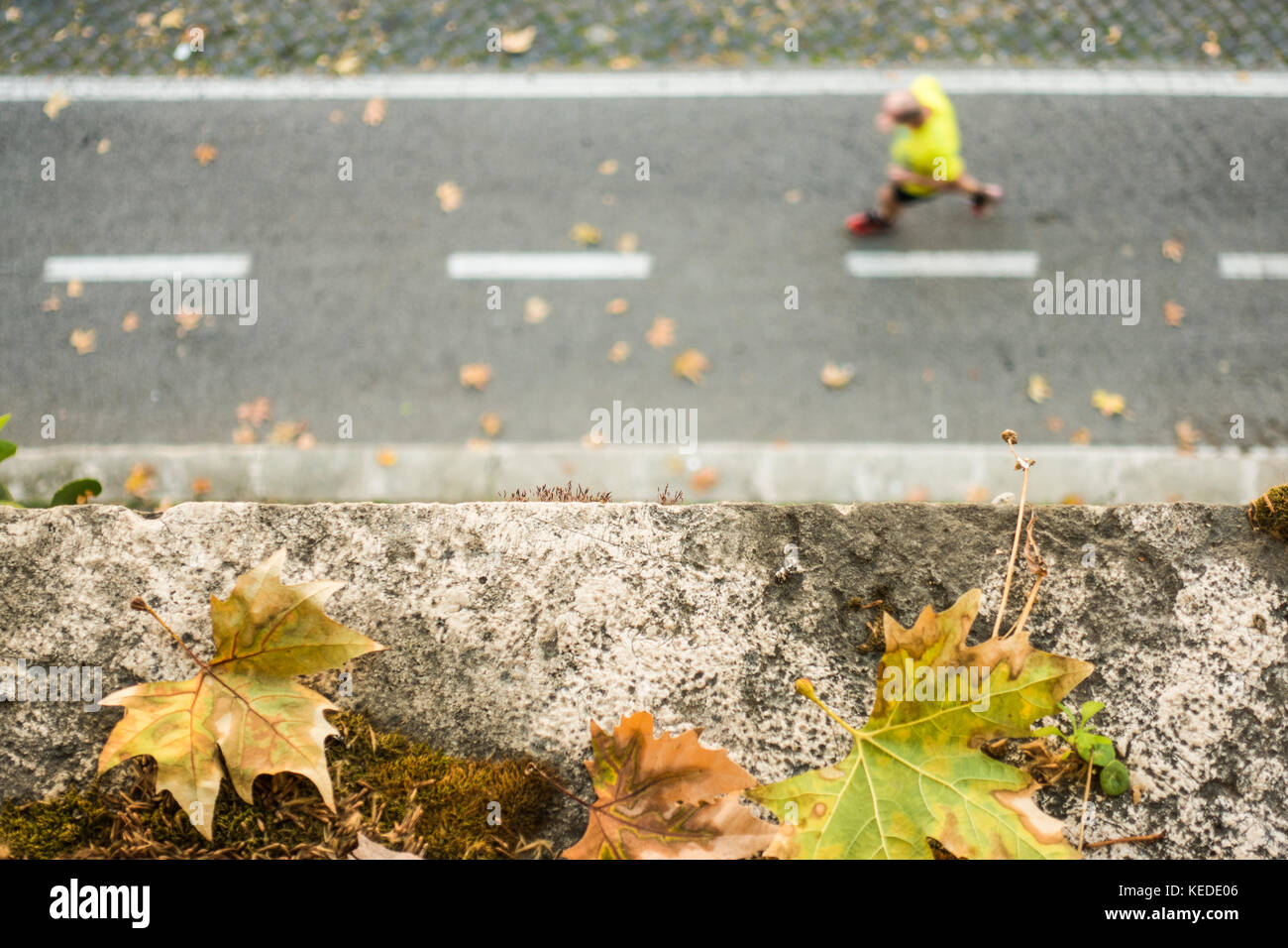 -Selective Focus- View from above, defocused/blurred person with a yellow t-shirt  is running on a pedestrian track. - Stock Image