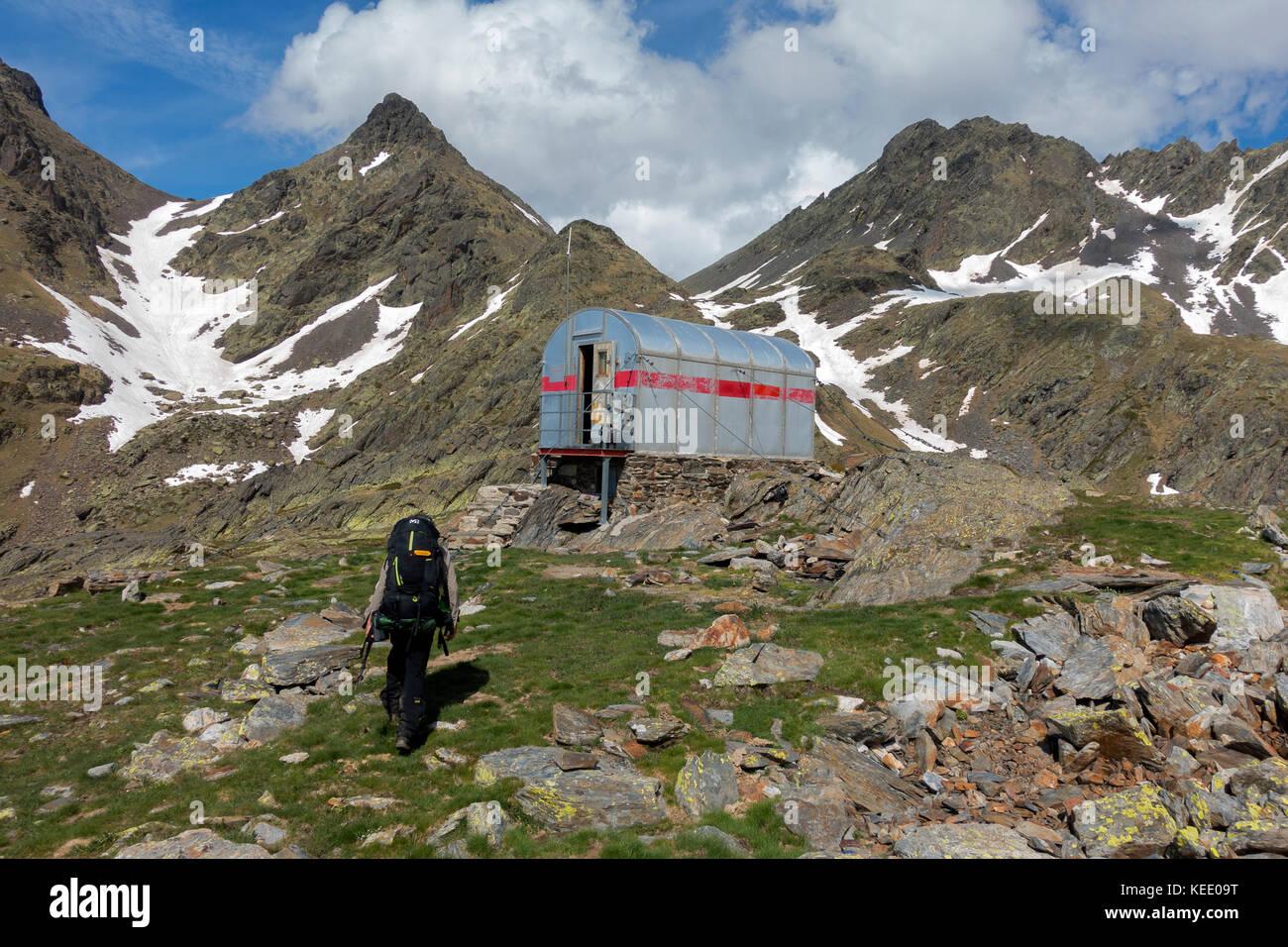 Trekker approaching to Monfort shelter.Pyrenees.Catalunya.Spain - Stock Image