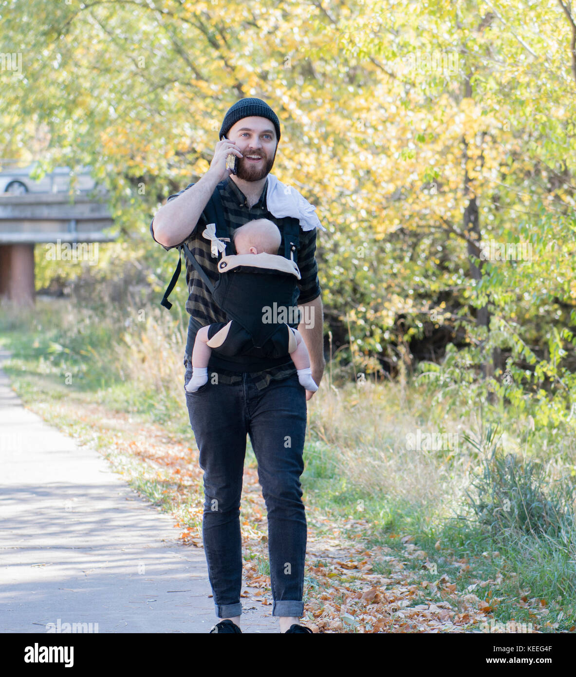 Millennial Dad with Baby in Carrier Outside Talking and Texting - Stock Image