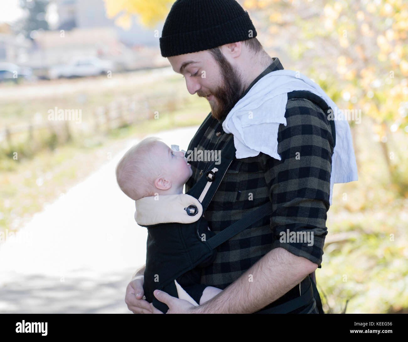 Millennial Dad with Baby in Carrier Outside Walking - Stock Image