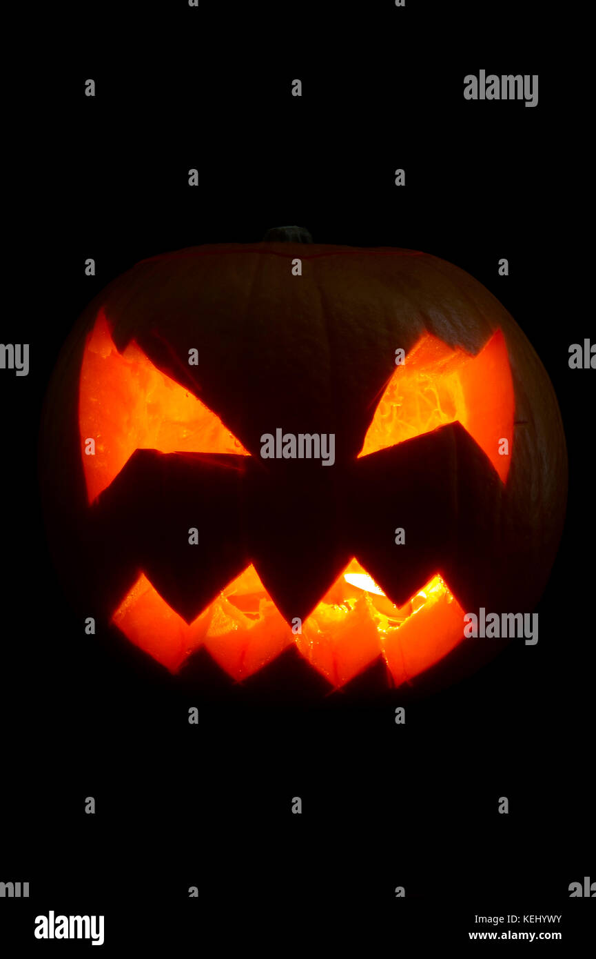 A traditional scary glowing face carved into a Halloween Pumpkin or Jack o'lantern on a black background - Stock Image