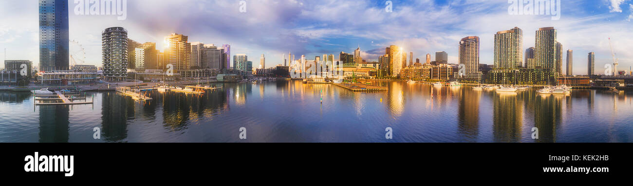 Docklands suburb of Melbourne surrounding still water bay on Yarra river with tall high-rise residential and business - Stock Image