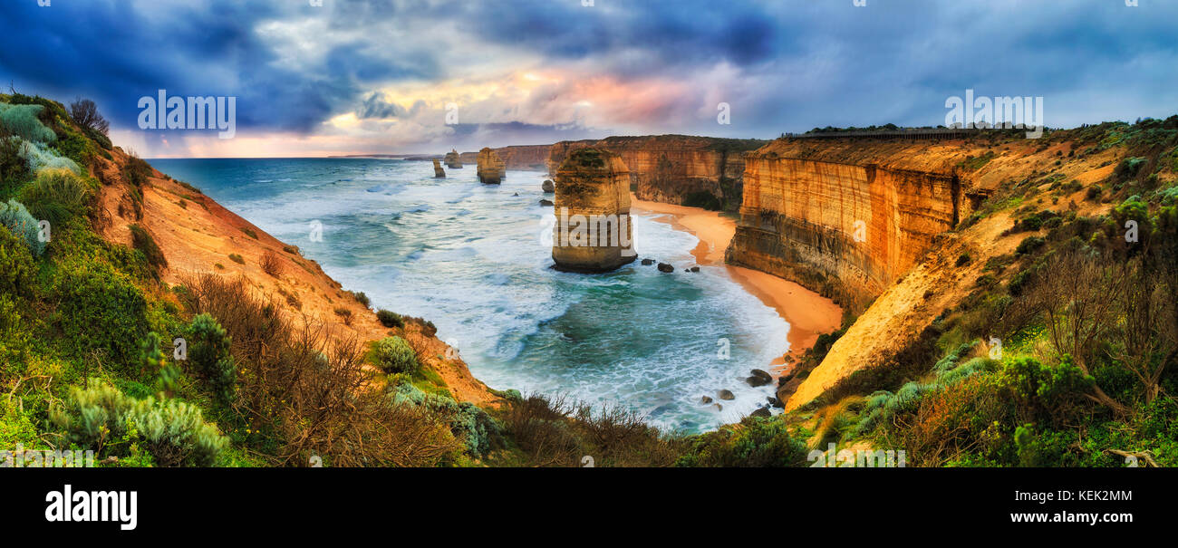 Stormy colourful sunset over twelve apostles marine park on Great Ocean road from lookout towards limestone standing - Stock Image