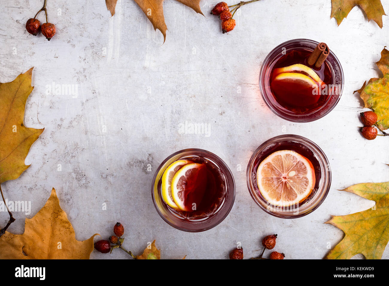 Hot red tea with lemon on light gray table with copy space viewed from above, delicious autumn mulled wine drink - Stock Image