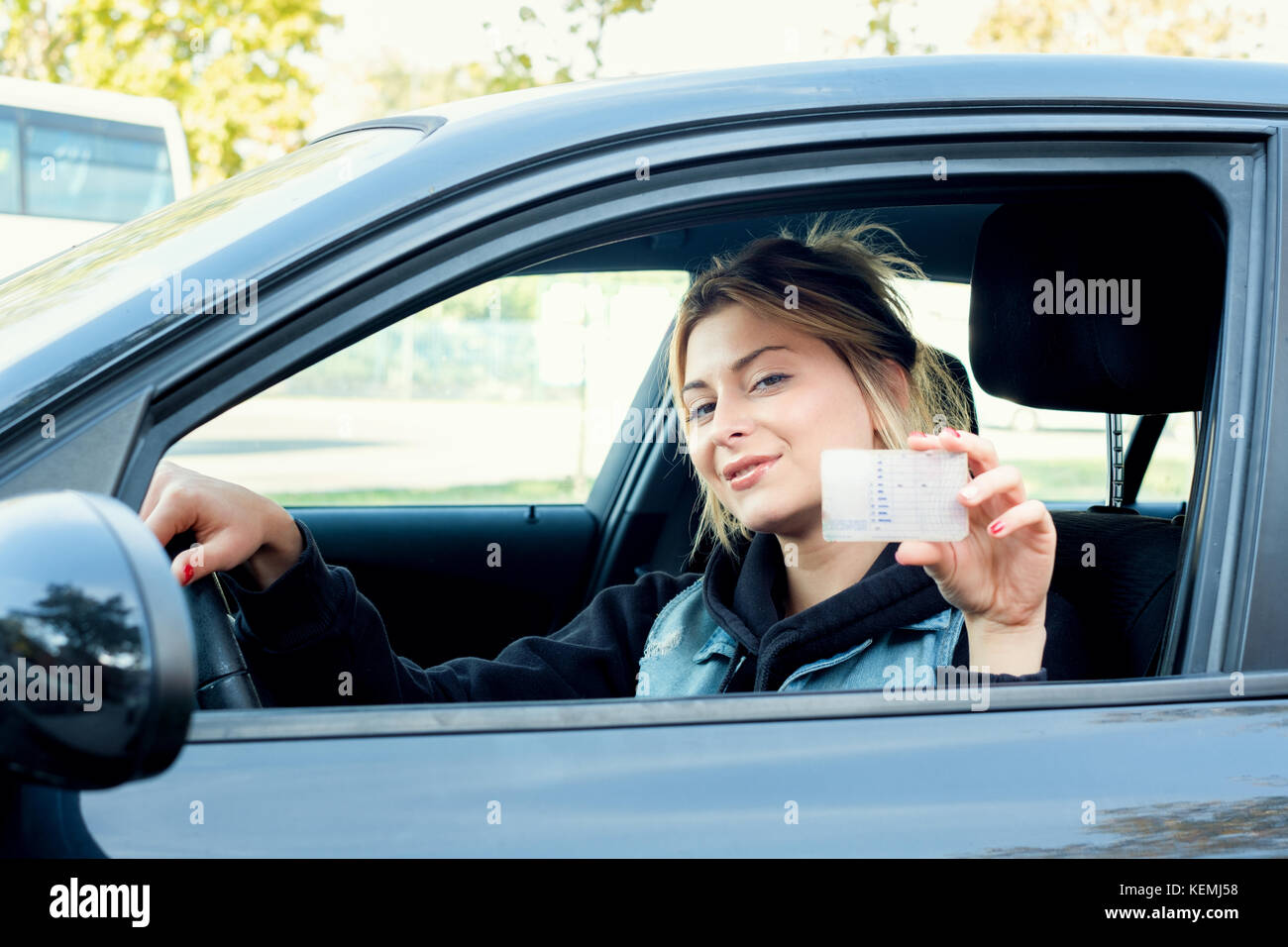 Young girl holding her new driving license seated in the car - Stock Image
