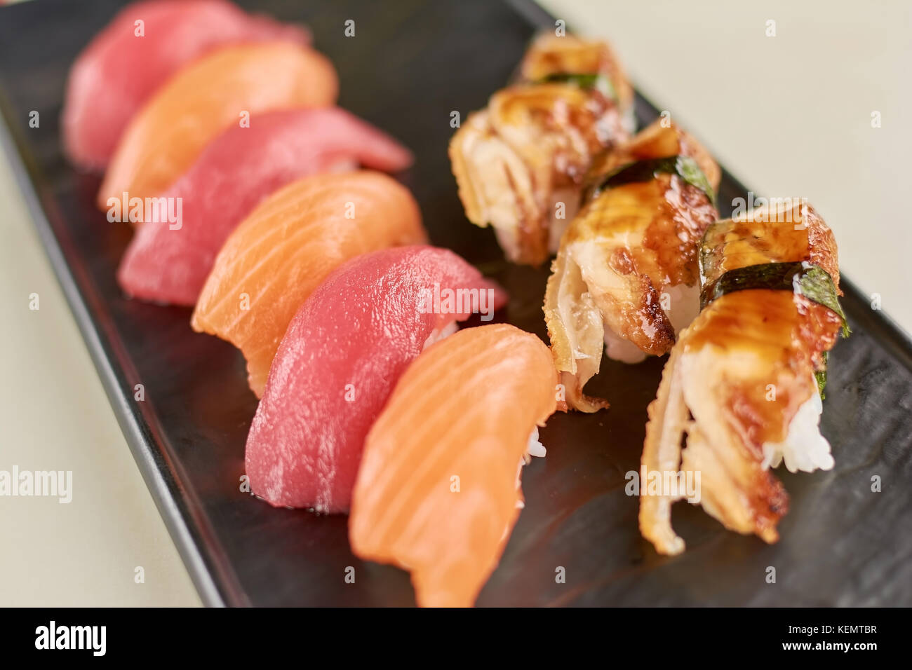 Sushi nigiri with salmon, tuna and eel. Close up of delicious sushi with fish on plate. Restaurant of seafood. - Stock Image