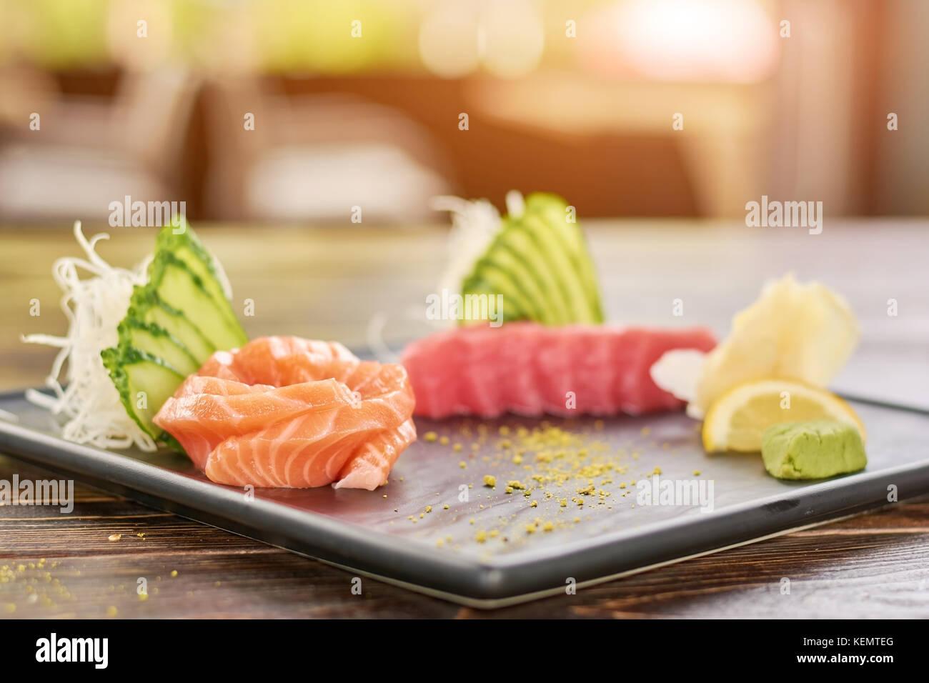 Fresh fish sashimi set. Raw salmon and tuna sashimi served with cucumber, salmon and wasabi. - Stock Image