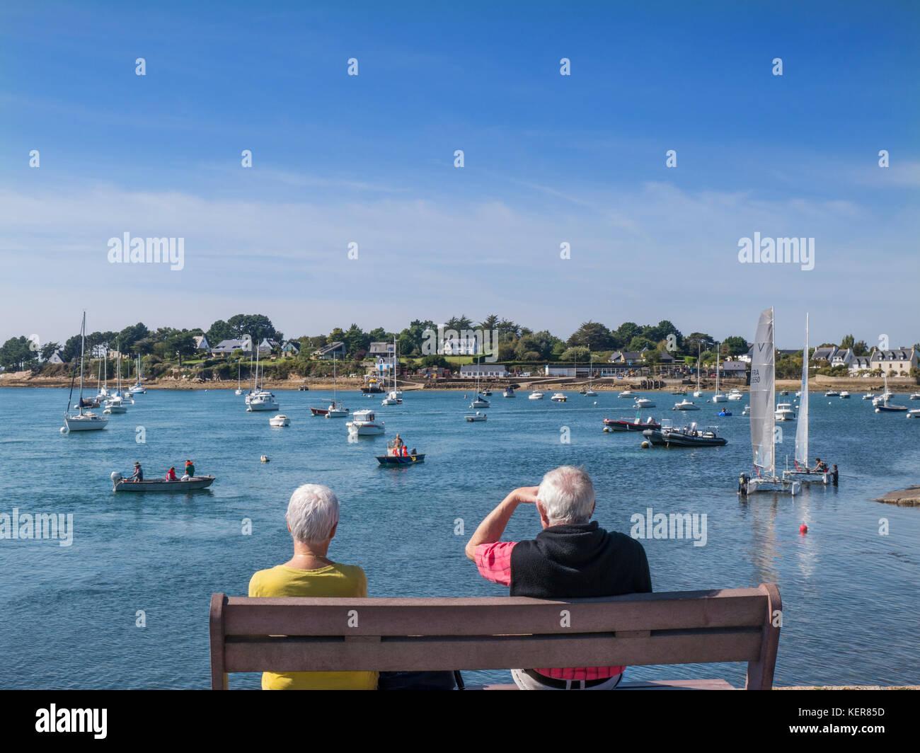 Mature couple sitting on bench at Sentier de la Plage, watching various boating activities Golfe du Morbihan, Larmor - Stock Image