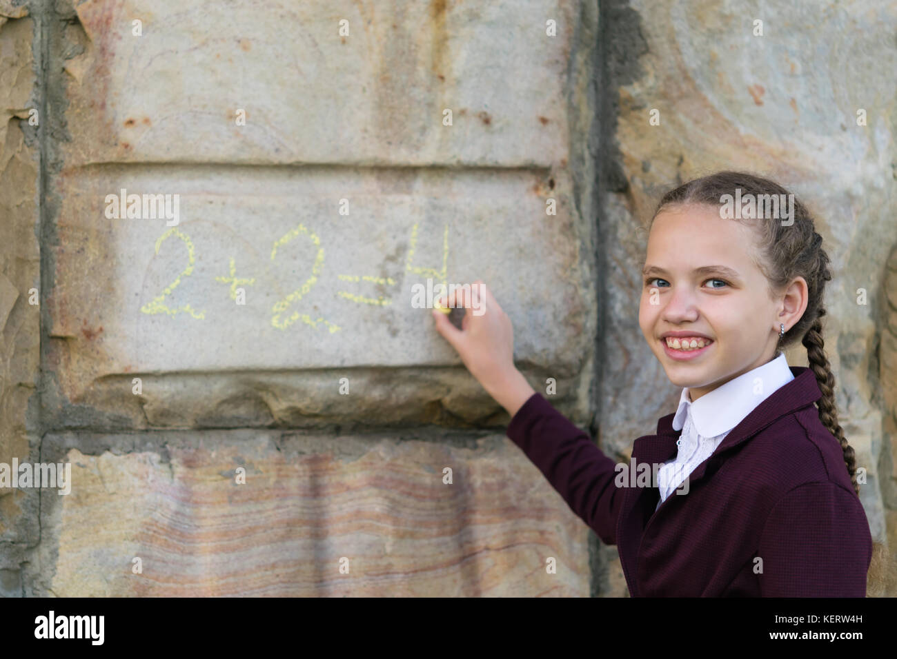 girl from school decides for example on the wall - Stock Image