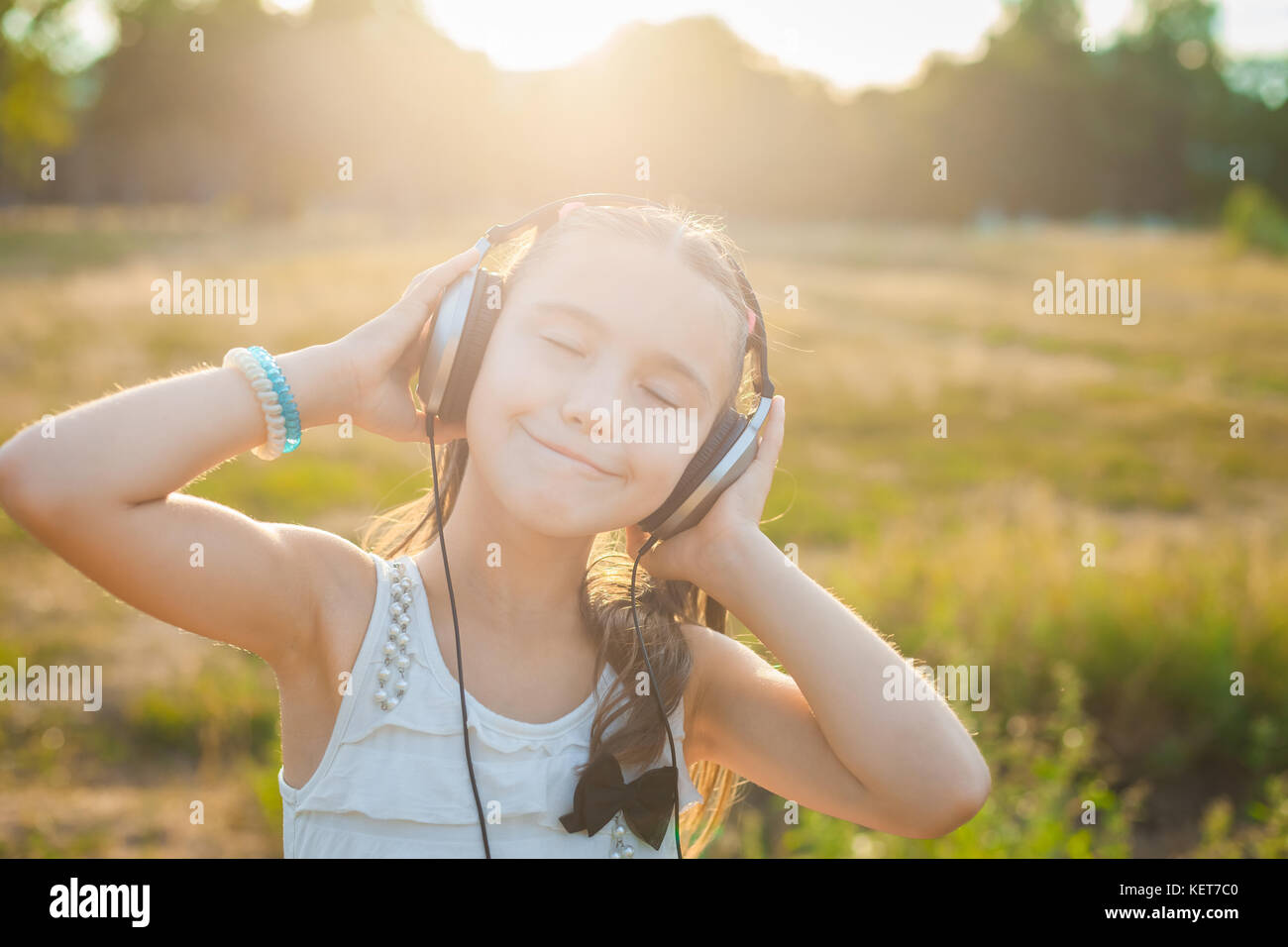 Funny girl listening music with headphones - Stock Image