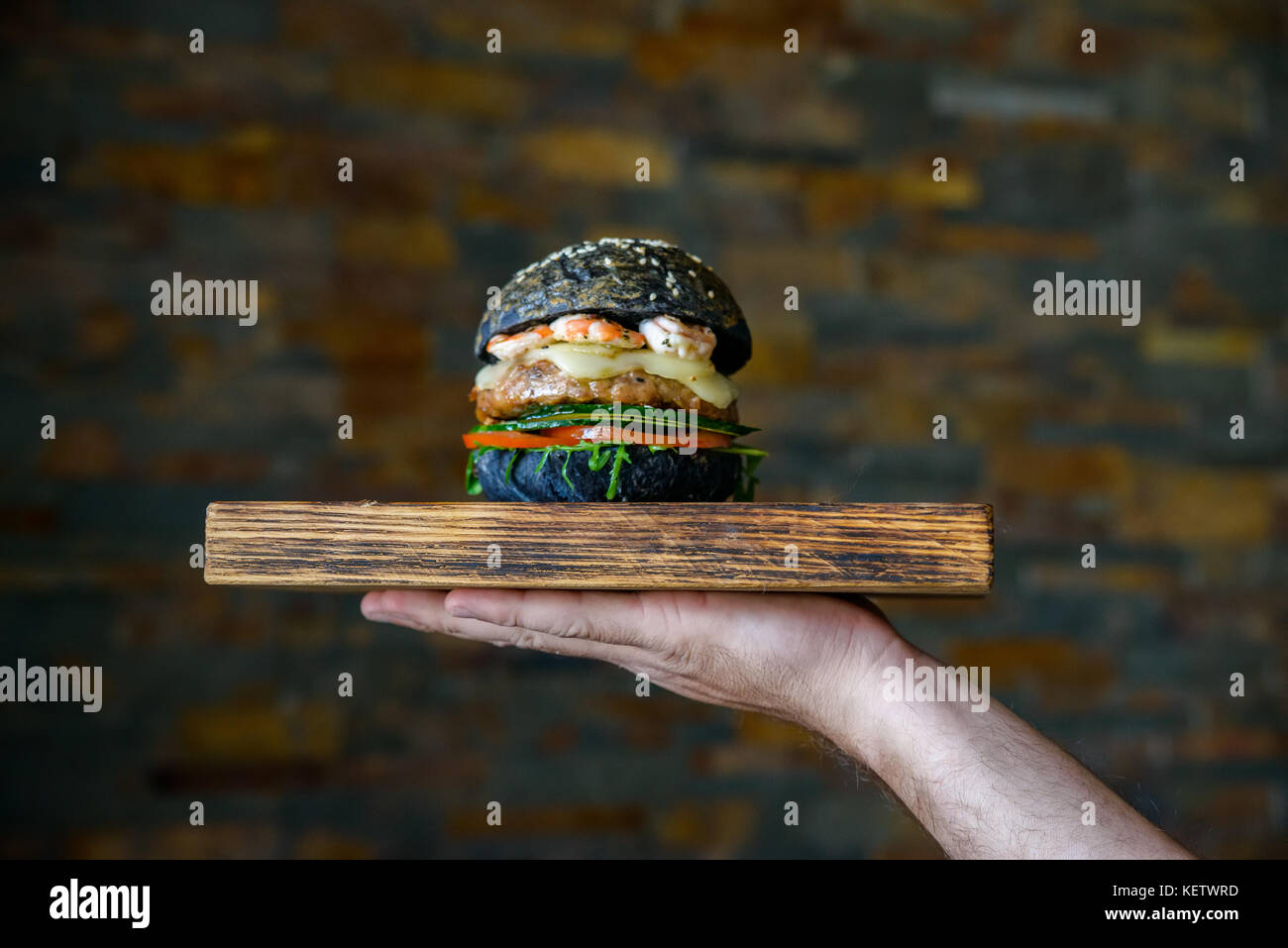 Waiter holds burger with prawns on wooden board - Stock Image