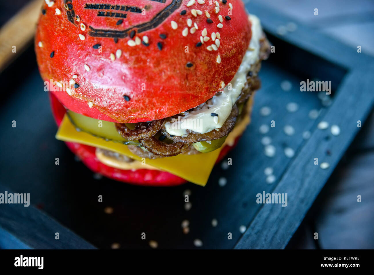 Black burger with prawns on wooden board - Stock Image
