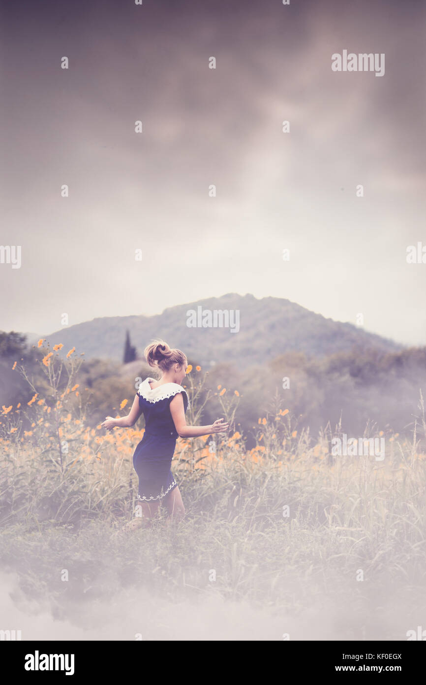 Girl running in a field at dusk, with smoky fog around her - Stock Image