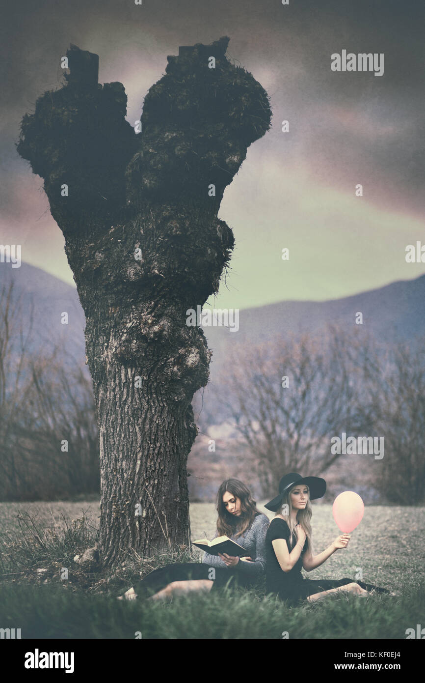 Opposites: two girls sitting under a tree, one holding a pink balloon, the other holding a book - Stock Image