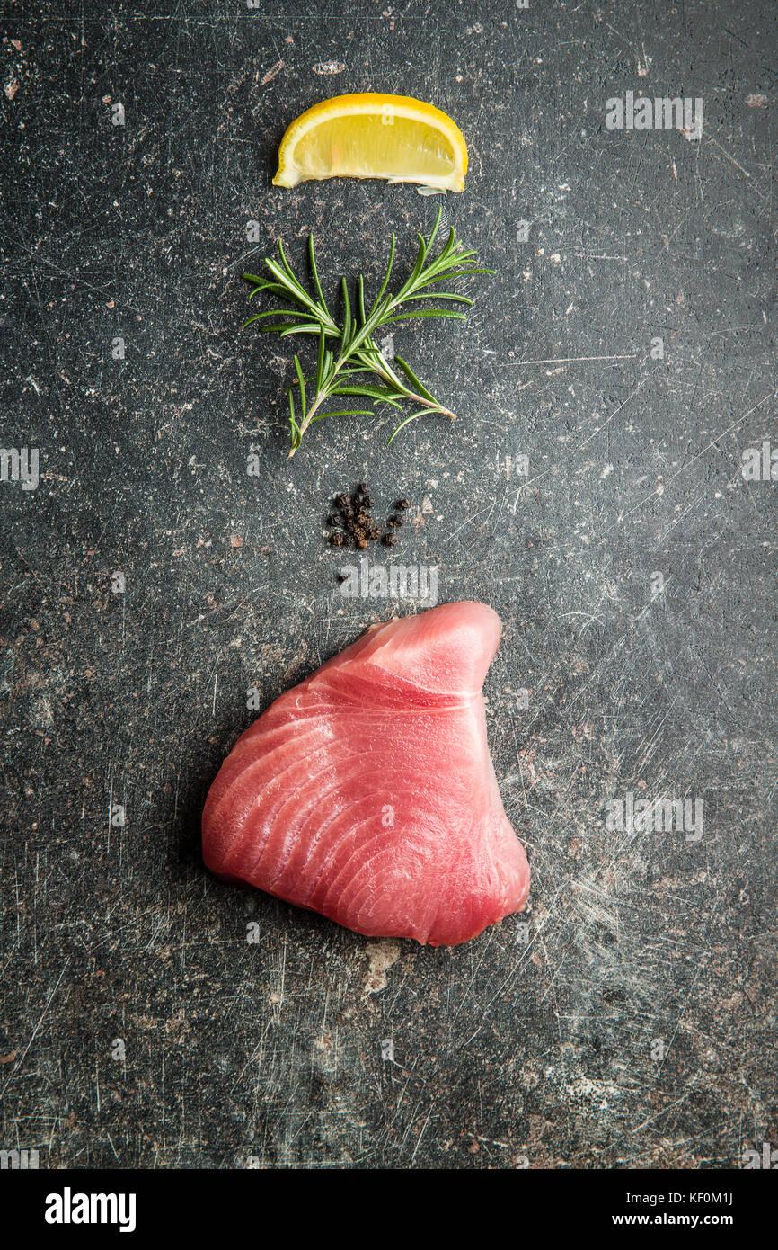 Fresh raw tuna steak on old kitchen table. - Stock Image