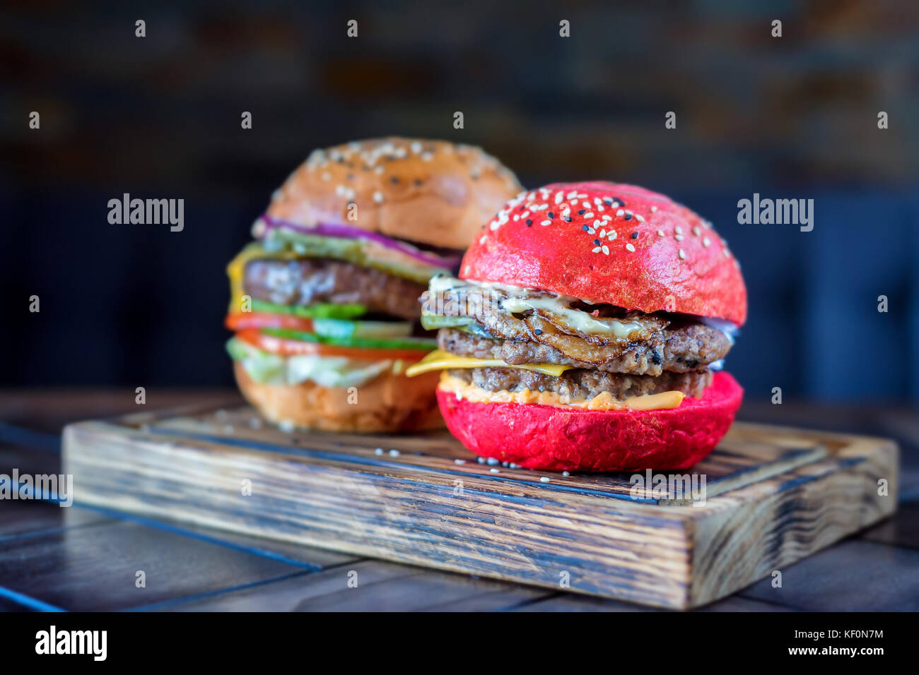 Two different restaurant burgers on wooden board - Stock Image