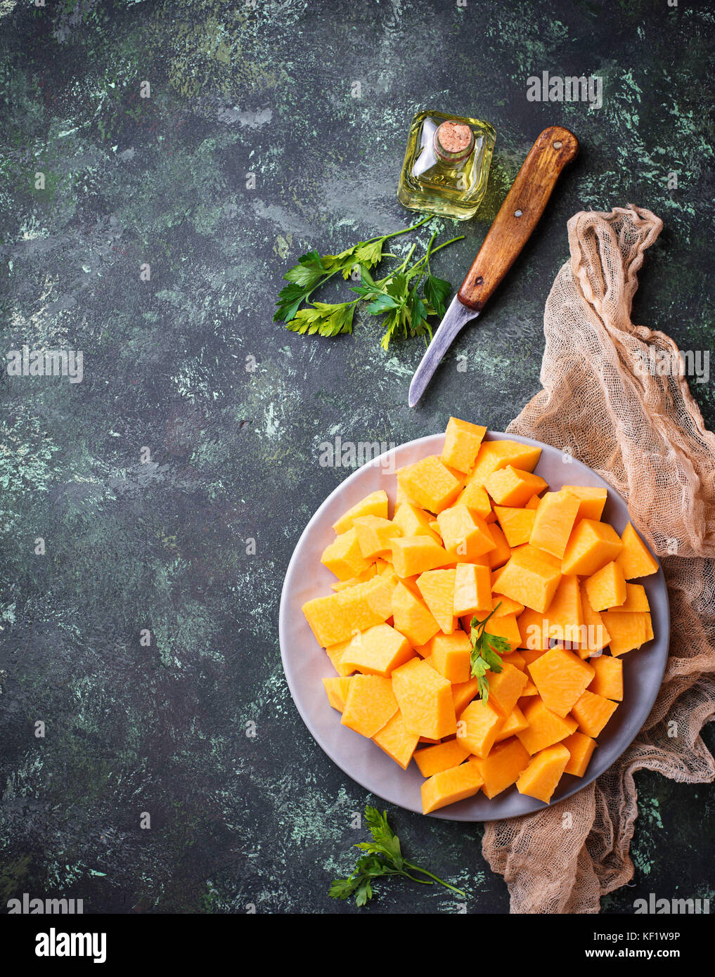 Raw chopped pumpkin on concrete background - Stock Image