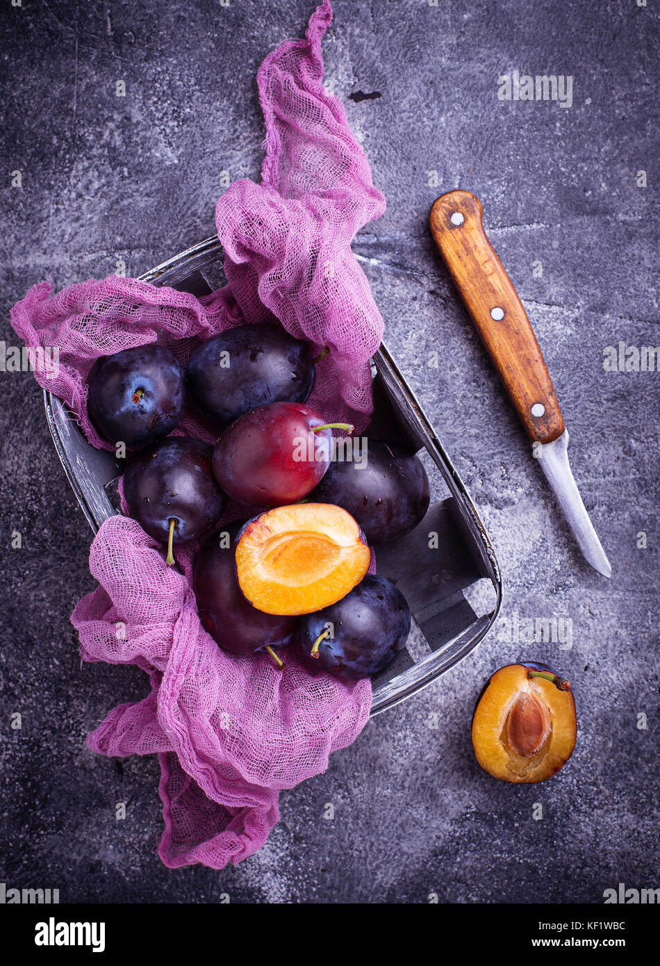 Fresh sweet plums on concrete background - Stock Image