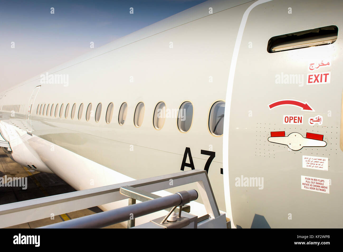 The fuselage of a large Boeing plane on the tarmac at an international airport. - Stock Image
