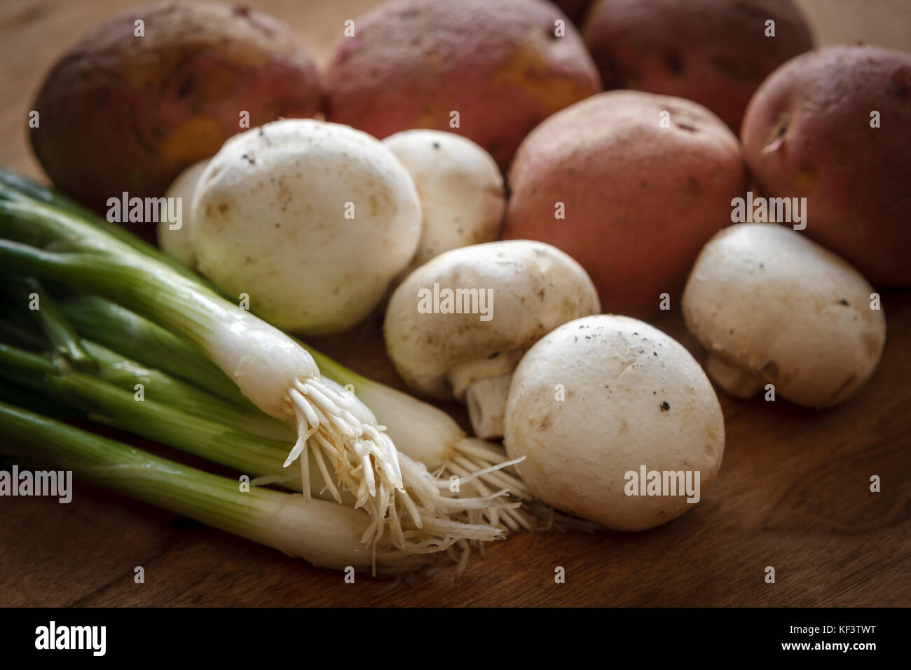 A close up image of vegetables like green onions, mushrooms, and red potatoes used in cooking. - Stock Image