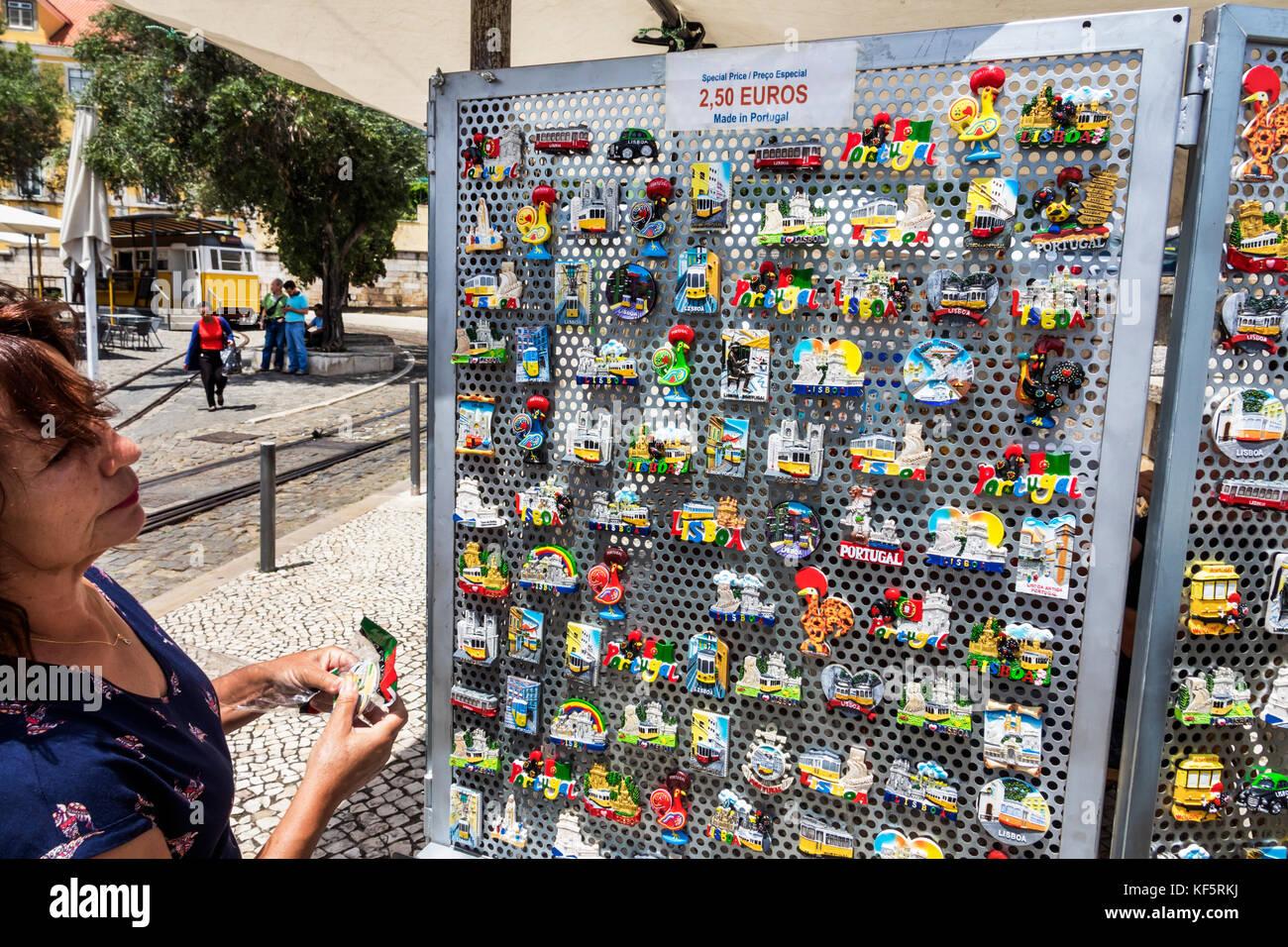 Lisbon Portugal Belem historic district Rua de Belem street vendor souvenirs refrigerator magnets woman shopping - Stock Image