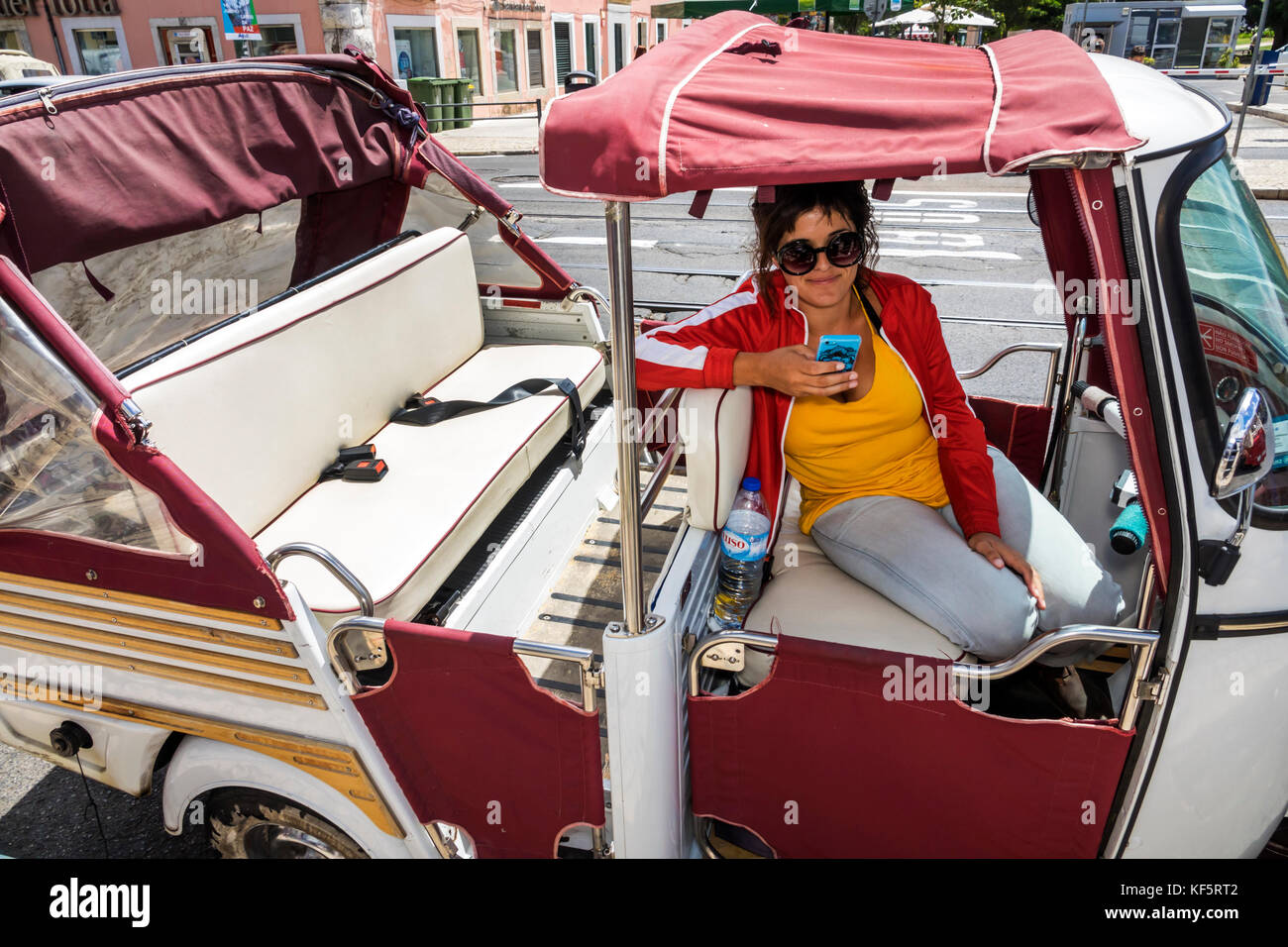 Lisbon Portugal Belem historic district Rua de Belem tuk-tuk tricycle cycle rickshaw woman driver waiting smartphone - Stock Image