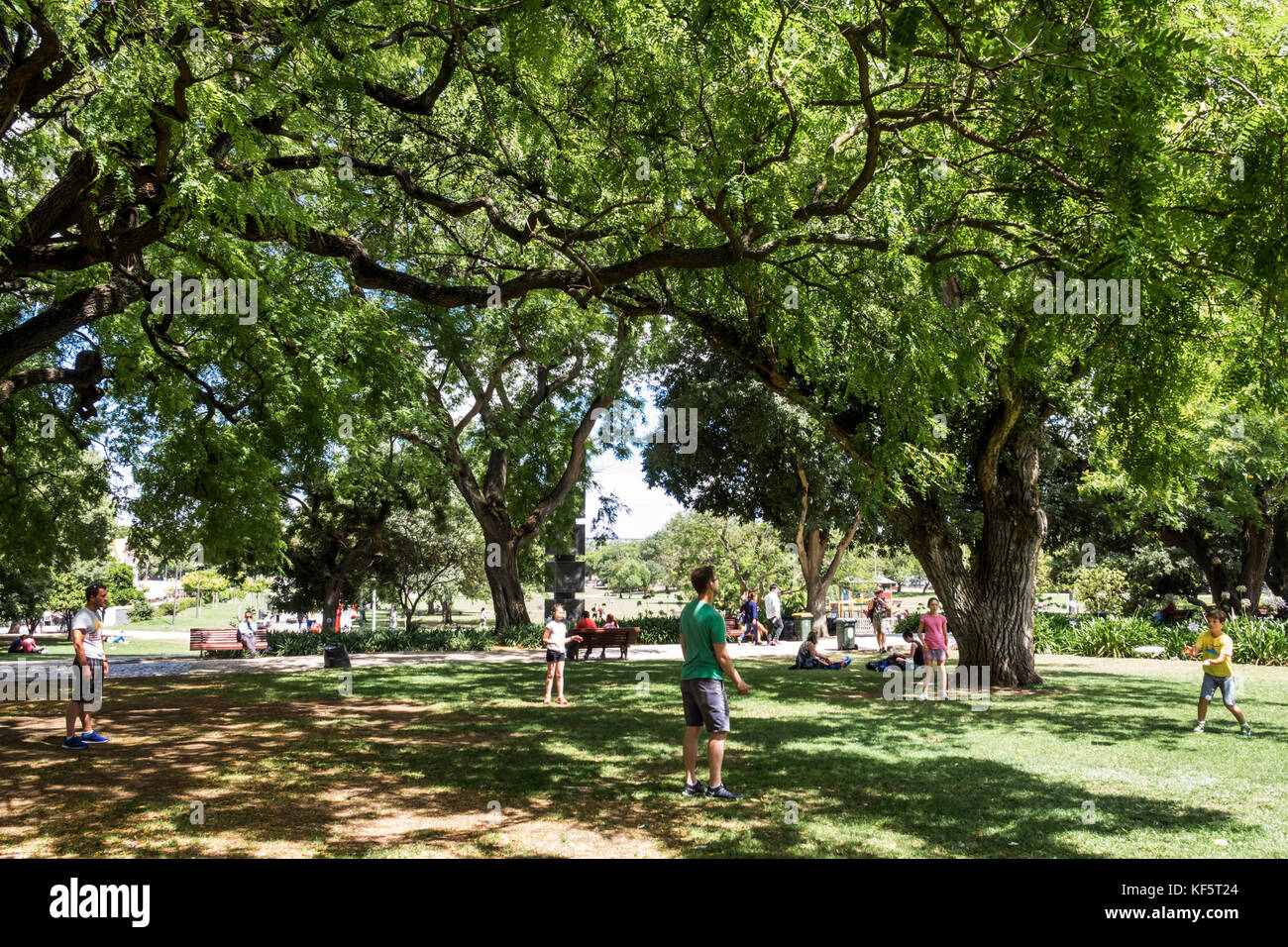 Lisbon Portugal Belem historic district Jardim Vasco da Gama urban park lawn trees man boy girl Hispanic family - Stock Image
