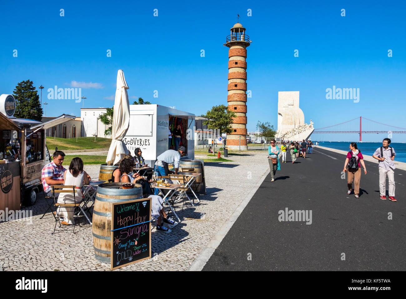 Lisbon Portugal Belem Tagus River waterfront promenade lighthouse food vendor bar tapas Happy Hour tables man woman - Stock Image
