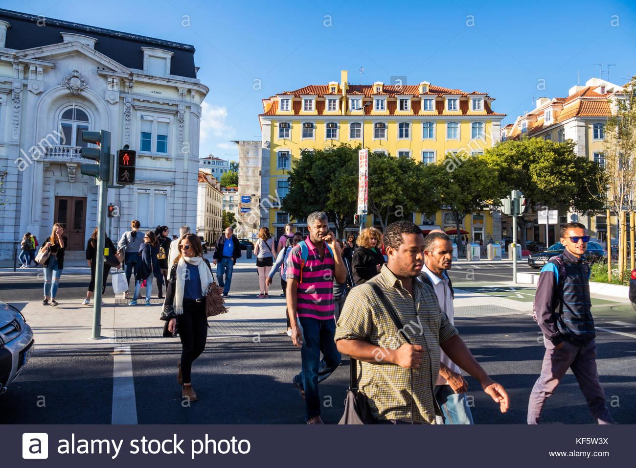 Lisbon Portugal Cais do Sodre street crossing pedestrian Black man woman residential apartment buildings - Stock Image